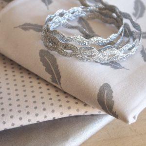 Tissu petites plumes argent scintillant
